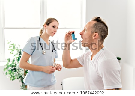 medical doctor applying oxygen treatment on a sporty men stock photo © lopolo