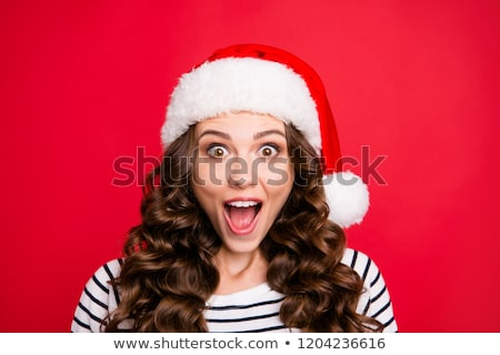 Portrait of joyful woman wearing Santa Claus red hat wondering a Stock photo © deandrobot