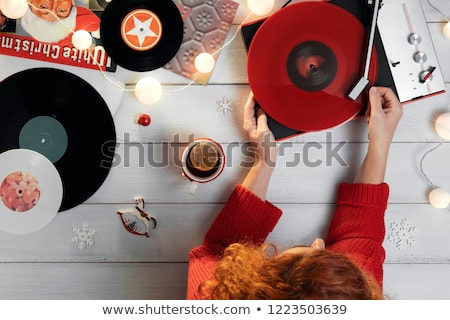 Woman putting needle on vinyl record on turntable Foto stock © Kzenon