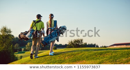 couple carrying golf bag while walking on golf course stock photo © kzenon