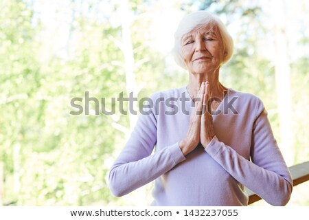 Stock photo: Pretty grandma in casualwear keeping her hands put together by chest