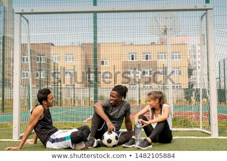 Three young intercultural friendly soccer players sitting by net on green grass Stock photo © pressmaster