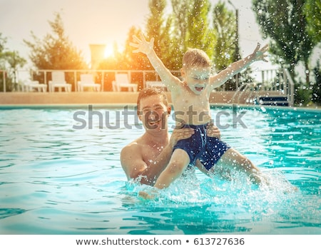 young cheerful father and son in a swimming pool stock photo © galitskaya