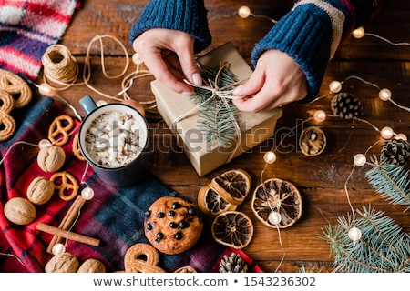 Zdjęcia stock: Hands Of Girl Making Bow On Top Of Wrapped Giftbox Surrounded By Xmas Stuff