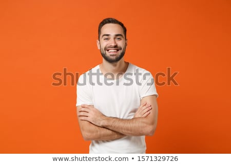 Masculine stylish modern man in orange t-shirt, hold hands in pockets and smiling friendly, come hel Stock photo © benzoix