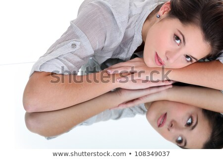 Young woman resting her head on a mirrored surface Stock photo © photography33