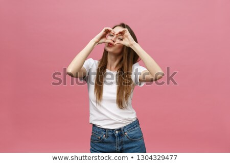 Smiling woman making a heart gesture Stock photo © AndreyPopov