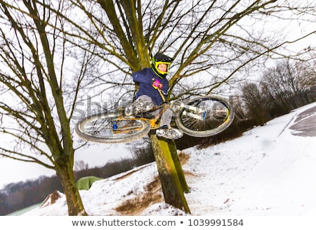 boy jumping with his bike over a ramp in snow Stock photo © meinzahn