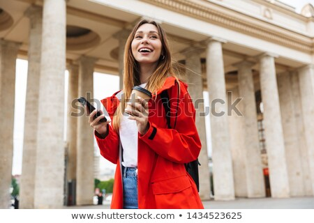 Beautiful red hooded woman drinking coffee and using mobile phon Stock photo © stevanovicigor