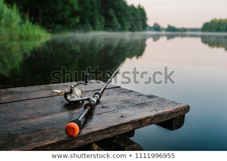 fishing rod, lure, and hook on jetty  Stock photo © Kzenon