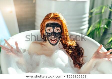 Attractive having green cream on her face at spa center Stock photo © wavebreak_media