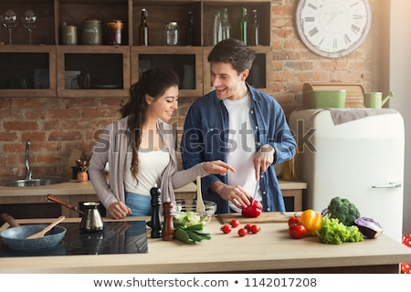 loving couple standing at kitchen and cooking together stock photo © deandrobot