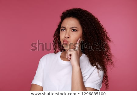 Concentrated young woman with shaggy hair touching her chin with Stock photo © deandrobot