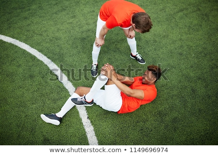 young man helps hurt soccer player Stock photo © bluering