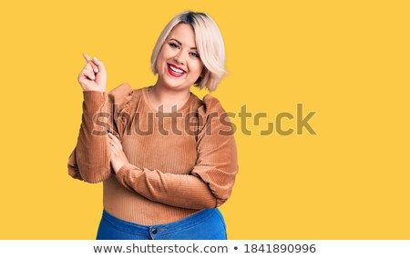 emotional plus size model standing in studio with open mouth screaming showing agression anger want stock photo © traimak