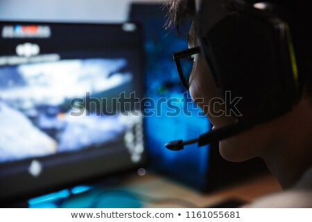 Stock photo: Photo closeup of obsessed gamer boy playing video games online o