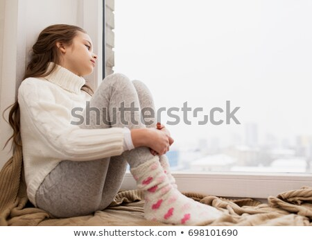 sad girl sitting on sill at home window in winter Stock photo © dolgachov