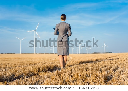 Investor in wind turbines with computer evaluating her investment on site Stock photo © Kzenon