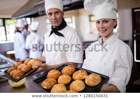 Male and female chefs holding baking tray of kaiser rolls in kitchen at hotel Stock photo © wavebreak_media