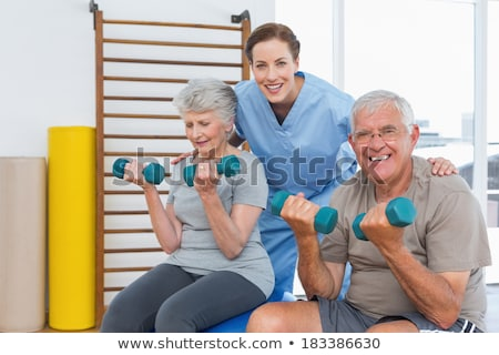 Stock photo: Front view of a female doctor and senior couple looking and discussing over clipboard they hold in t