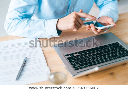 Young employee in shirt sitting in front of laptop and scrolling in smartphone Stock photo © pressmaster