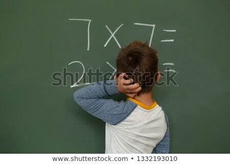 Rear view of Caucasian schoolboy doing math on greenboard in a classroom at elementary school Stock photo © wavebreak_media