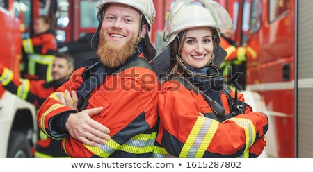Fire fighter man and woman standing shoulder to shoulder Stock photo © Kzenon
