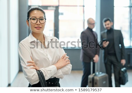 Young successful business traveler with hangbag on crossed arms looking at you Stock photo © pressmaster