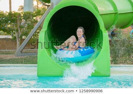 Happy woman going down a water slide Stock photo © galitskaya