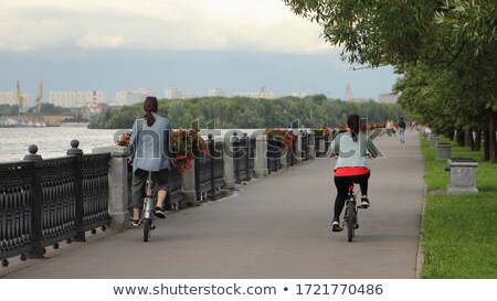 Stock photo: young couple riding bikes along a river