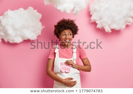Pregnant woman looking at baby cloth, rejoicing Stock photo © stockyimages