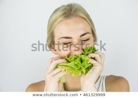 Blond woman eating lettuce leaf stock photo © photography33