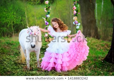 Woman in dress swings on children horse Stock photo © vetdoctor