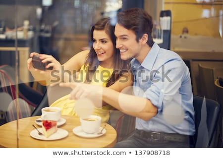 Couple Looking At Photographs On Camera At Restaurant Stock photo © unkreatives
