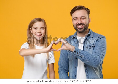 smiling little girl showing heart with hands stock photo © dolgachov