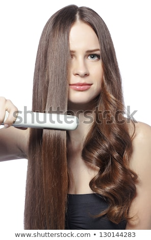 Woman doing hairstyle with hair straightener  Stock photo © deandrobot