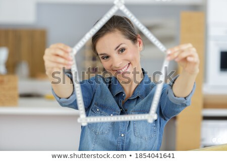 young female forming house from folding rule stock photo © nyul
