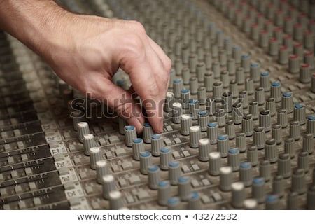 Sound producer rotating a regulator of old dirty sound mixer pult Stock photo © Paha_L