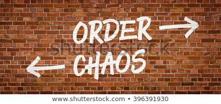 Sipariş kaos yazılı tuğla duvar boya ok Stok fotoğraf © Zerbor