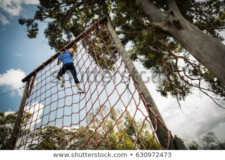 Stock photo: Fit woman climbing a rope during obstacle course
