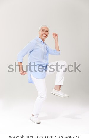 Full-length portrait of playful mature woman in blue shirt and w Stock photo © deandrobot