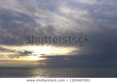 a passenger plane flying in the sky over the sea v Stock photo © dmitriisimakov