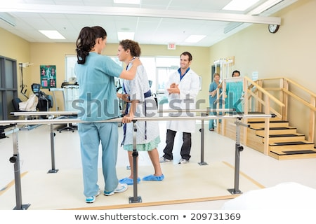 Therapist Assisting Patient While Walking In Clinic Stock photo © AndreyPopov
