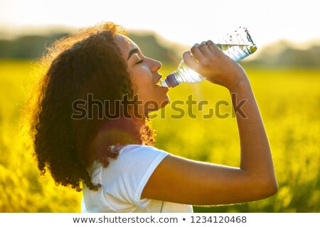 Young women in yellow sport shirt are drinking water at the gym Stock photo © boggy