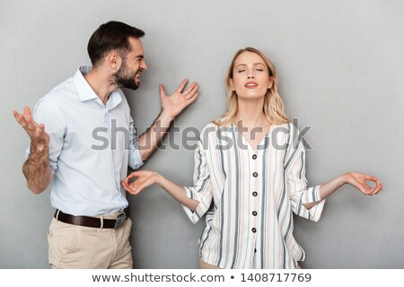 Photo of angry man and woman in casual clothes screaming at each Stock photo © deandrobot