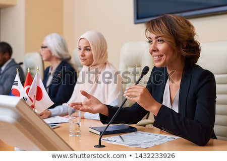 Happy young female delegate in formalwear looking at audience Stock photo © pressmaster