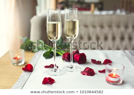 happy couple with bottle of champagne and glasses stock photo © dolgachov