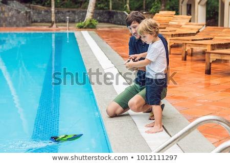 Homem jogar remoto barco piscina família Foto stock © galitskaya