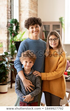 Young brunette woman and her daughter in casualwear standing by shop window Stock photo © pressmaster