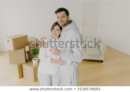 Millennial couple with plesant smiles, hug and hold key from own apartment, buy their first home, mo Stock photo © vkstudio
